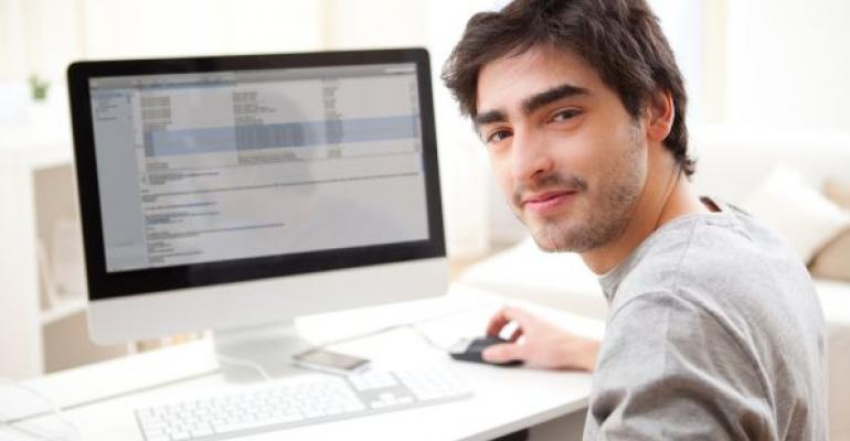 Young man smiling while working on computer