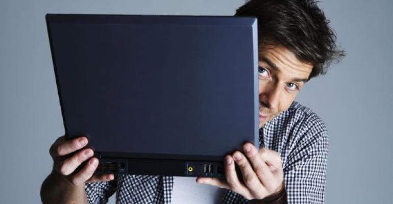 man peeking out behind a laptop