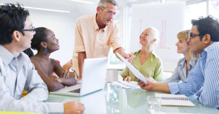 older man giving career advice to group of younger workers