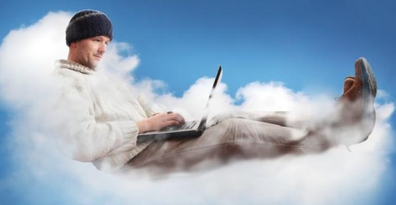 Man sitting on cloud working on laptop