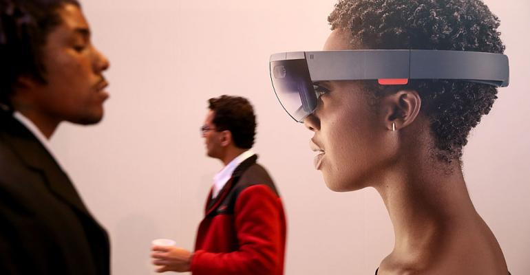 Attendees walk by an image of the Microsoft HoloLens augmented reality AR viewer during the 2016 Microsoft Build Developer Conference