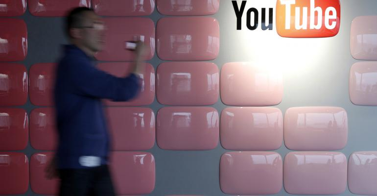 A young man walks by a YouTube corporate logo.